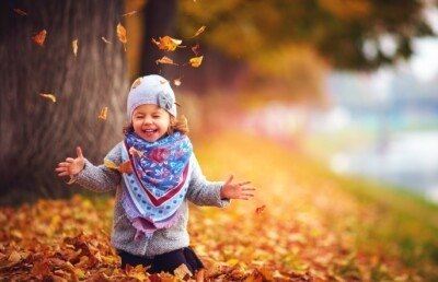 Smiling little girl playing in leaves.