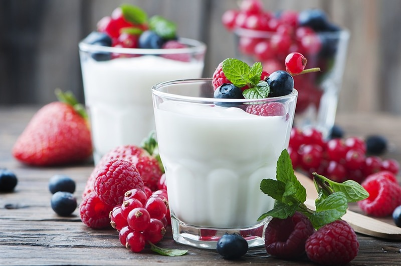 A photo of yogurut in a cup with berries