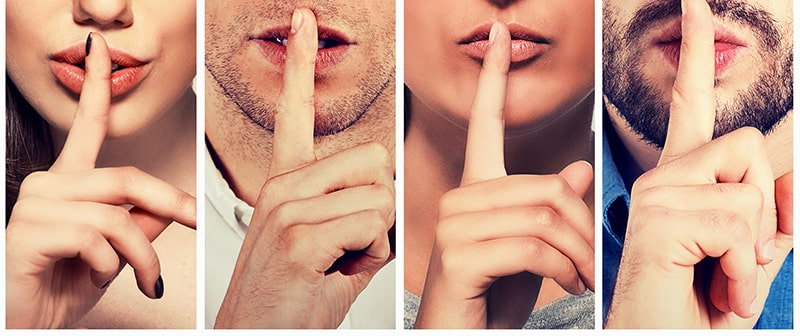 Four individuals with their finder up to the lips as if to cover up a secret.