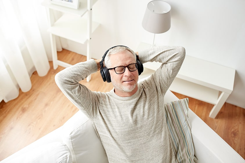 Man resting with his eyes closed while listening to his NuCalm device for his consultation with Dr. Pamela Marzban
