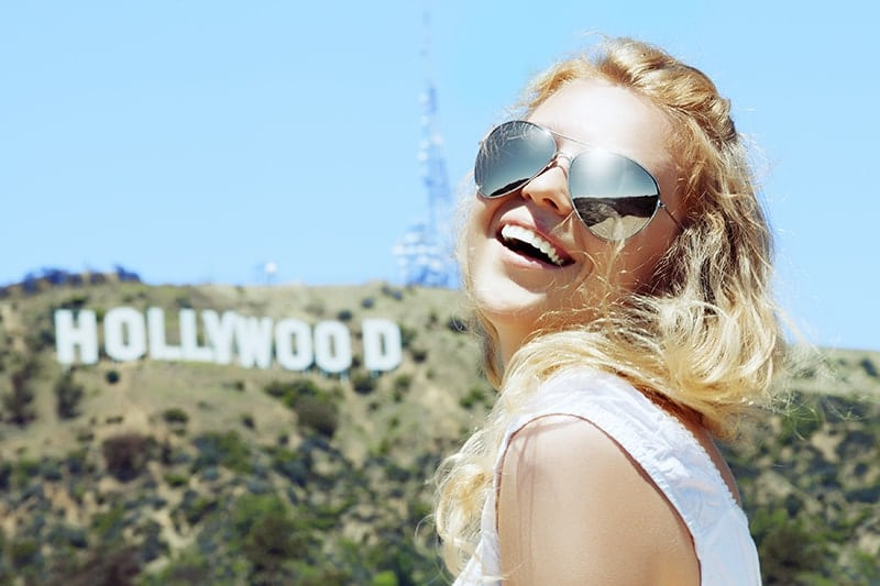 A pretty blonde woman in big sunglasses stands in front of the Hollywood sign. While Hollywood is the standard for cosmetic dentistry the new trend is a more natural, beautiful look to your smile. Learn how Dr. Marzban can make you beautiful!