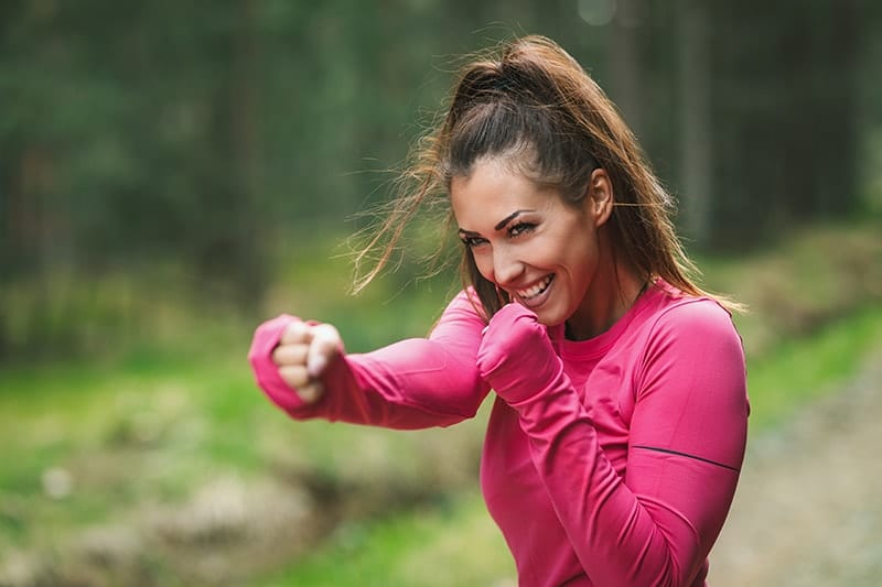 A woman in a pink workout shirt shadow boxes outside in nature. With workouts she's building her strength, with Myofunctional Therapy she's Strengthen Muscles of the Mouth and Face.