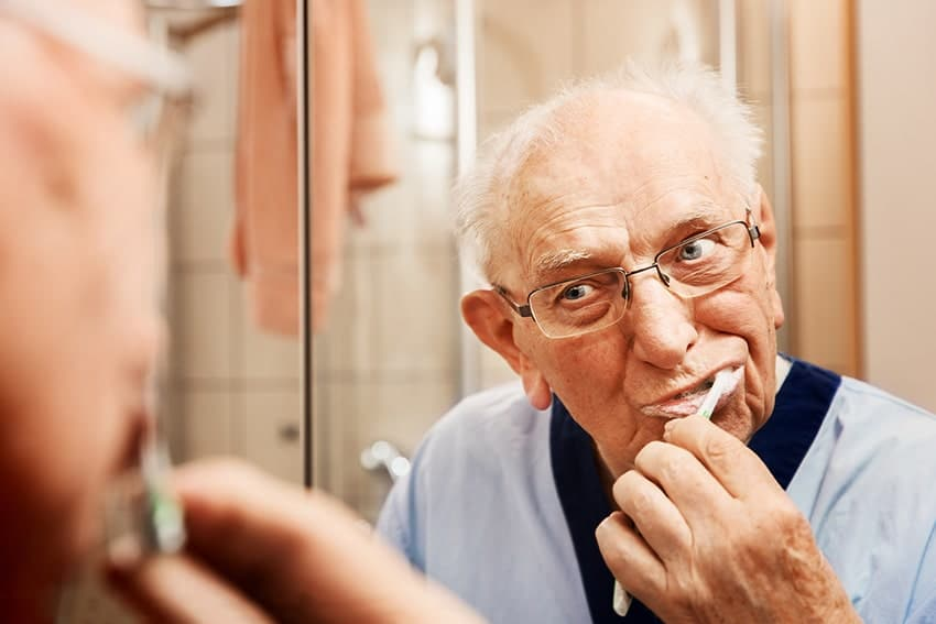 An older man brushes his teeth in front of a mirror in the bathroom